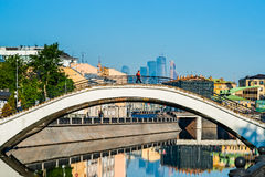 Arch bridge over the river. MOSCOW, RUSSIA - MAY 25, 2015: Arch bridge over the bypass canal of the Moscow river. Unidentified person crosses the bridge Royalty Free Stock Image