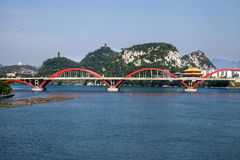 Arch bridge on river with natural landscape,Liuzhou,China. Red arch bridge (Wenhui bridge ) in Liujiang River with the Panlong Hill in the background ,Liuzhou Stock Photography