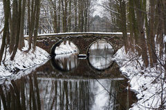 Arch bridge in snowy winter park. Foot arch bridge and its reflection in river at snowy winter weather Royalty Free Stock Photography
