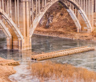 Arch bridge with spandrel columns spanning a river. With a smaller bridge with pieces missing Stock Image