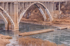 Arch bridge with spandrel columns spanning a river Stock Photography