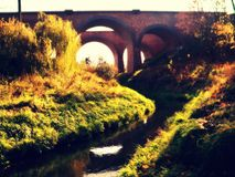 Arch bridge in sun. Brick rail arch bridge over the river Lutryna Royalty Free Stock Photo