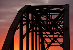 Arch bridge in sunset. Abstract image of arched bridge against orange and red sky Stock Photo