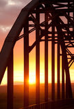 Arch bridge in sunset. Arched bridge with beams and framework against orange and red sky Royalty Free Stock Photography