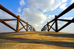 Arch bridge under the clouds. Wooden arch  bridge under the sky and clouds Royalty Free Stock Image