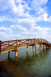 Arch bridge under the clouds. Wooden arch  bridge under the sky and clouds Royalty Free Stock Photo