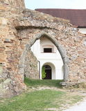 Arch in broken wall on Velhartice Castle. Gothic arch of old gate in broken stone wall with white renaissance palace behind on Velhartice Castle in Czech Stock Images
