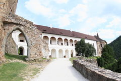Arch in broken wall on Velhartice Castle. Gothic arch of old gate in broken stone wall with white renaissance palace behind on Velhartice Castle in Czech Royalty Free Stock Photography
