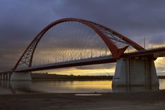 Arch of the Bugrinsky bridge against the background of a contrasting dawn sky royalty free stock photography