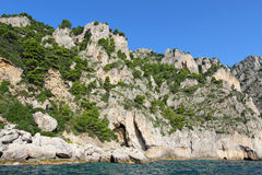 An arch and caves on the coast of Capri island, Italy. A natural arch and several small caves on the east coast of the island of Capri, Italy, viewed from the Stock Photography