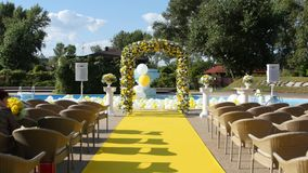 Arch and chairs prepared for an outdoor ceremony stock footage