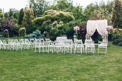 Arch and chairs for the wedding ceremony. Decorated with cloth and floral compositions Royalty Free Stock Photography