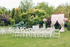 Arch and chairs for the wedding ceremony. Decorated with cloth and floral compositions Royalty Free Stock Images