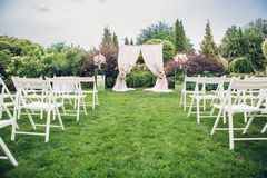 Arch and chairs for the wedding ceremony. Decorated with cloth and floral compositions Stock Image