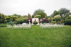 Arch and chairs for the wedding ceremony. Decorated with cloth and floral compositions Royalty Free Stock Image