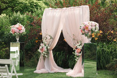 Arch and chairs for the wedding ceremony. Decorated with cloth and floral compositions Stock Photos
