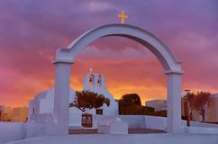 Arch, church and bell towers in Oia village, Santorini island, G. Reece on a sunrise with dramatic sky Royalty Free Stock Photo