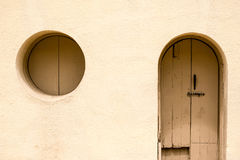 Arch and circle. An adobe building with an arched doorway and a circle window Royalty Free Stock Images