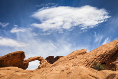 Arch and Cloud. Natural arch and white cloud, Valley of Fire State Park, Nevada, USA stock photo
