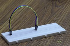 Arch of colored wires on a protoboard. A white bread board, on a wooden table, containing an Arch of colored wires Stock Photo