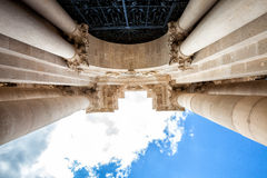 Arch and columns with capitals. Blue sky and clouds. Perspective photo of an old building with columns and capitals, wrought-iron door. blue sky with clouds Royalty Free Stock Image