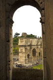 The Arch of Constantine as seen through an arch of the Coliseum. The Arch of Constantine as seen through an arch of the Coliseum in Rome, Lazio, Italy. Tourists Stock Photo