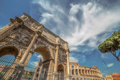 Arch of Constantine and Coliseum. View of the arch of Constantine, near the Coliseum in Rome, Italy. Sky with clouds in background Royalty Free Stock Photography