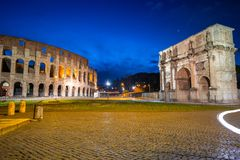 Arch of Constantine and the Colosseum illuminated at night in Rome, Italy. Roman coliseum ancient landmark travel history dusk architecture italian monument royalty free stock images