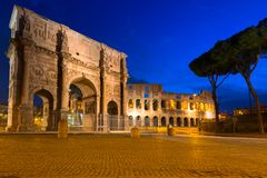 Arch of Constantine and the Colosseum illuminated at night in Rome, Italy. Roman coliseum ancient landmark travel history dusk architecture italian monument stock photo