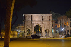 Arch of Constantine Italy Rome by night. Arch of Constantine in Italy Rome, with the Colosseum on the right and military vehicles in the foreground Royalty Free Stock Images
