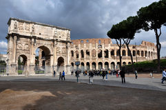 Arch of Constantine near the Colosseum in Rome, Italy. ROME, ITALY - MARCH 16, 2016: Tourist visiting the triumphal Arch of Constantine near the Colosseum in Royalty Free Stock Images