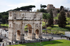 Arch of Constantine near the Colosseum in Rome, Italy. ROME, ITALY - MARCH 16, 2016: Tourist visiting the triumphal Arch of Constantine near the Colosseum in Royalty Free Stock Photo