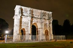 Arch of Constantine at night. The Arch of Constantine is a triumphal arch in Rome, situated between the Colosseum and the Palatine Hill Stock Photos