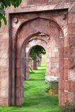 Arch corridor. Red arch corridor with green leaves in Indian style garden Royalty Free Stock Photo