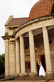 Arch Couple. A bride and groom next to a chapel Royalty Free Stock Photography