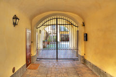 Arch and courtyard. Arched entrance to courtyard closed by metal gate Royalty Free Stock Images