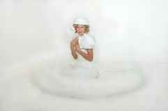 Arch and Coy. Bride flirts with two boa feather fans.  She is sitting in an all white room and wearing a hat with netting Royalty Free Stock Image