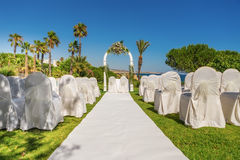 Arch and decorations for the wedding ceremony in the garden. With white chairs Stock Photo