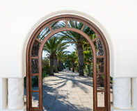 Arch door on the palm alley. Open doorway arch door on the alley of palm trees on a sunny summer day Royalty Free Stock Photos