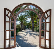 Arch door on the palm alley. Open doorway arch door on the alley of palm trees on a sunny summer day Stock Image