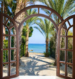 Arch door on the palm alley. Open doorway arch door on the alley of palm trees on a sunny summer day Stock Photo