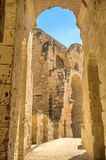 Through the arch. EL JEM, TUNISIA - SEPTEMBER 1, 2015: The Roman amphitheatre were built of the yellow tufa, a type of the limestone, on September 1, in El Jem Royalty Free Stock Image