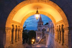 Arch in Fisherman`s Bastion, Budapest. Dusk view of Fisherman`s Bastion staircase thru round arch highlighted with Lantern Royalty Free Stock Photo