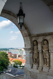 An arch at Fishermen` Bastion and a view to old buildings, a bridge and Danube river. At Budapest, Hungary Stock Image