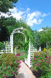 Arch in the garden. White arch in the beautiful garden Stock Photo