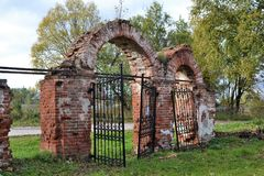 Arch with gates to the cemetery. Arch with a gate to the cemetery, the gates fall off, part of the building is overgrown with shrubs Stock Photo