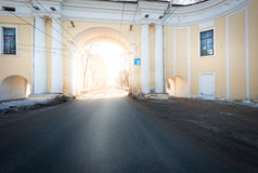 Arch house and asphalt road passing through it. Royalty Free Stock Photo