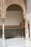 Arch with intricate stone carving, Alhambra Palace. Arch with intricate stone carving in Arabic and Moorish style and pillars off a courtyard in the Alhambra Royalty Free Stock Photography