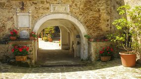 Arch. Italian yard. Flowers. Walls, stones Stock Image