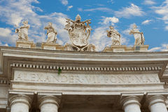 """Arch at near basilica of St Peter. Arch near Papal Basilica of St. Peter in the Vatican, Italy. The message on the arch is """"Alexander VII Pont Max Stock Photos"""